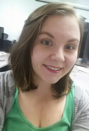 20ish girl with brown shoulder-length hair in a green tank top and gray sweater